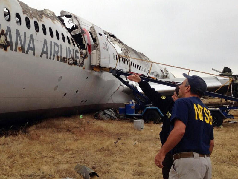 In this photo provided by the National Transportation Safety Board, on Tuesday, July 9, 2013, Investigator in Charge Bill English, foreground, and NTSB Chairwoman Deborah Hersman discuss the progress of the investigation into the crash of Asiana Airlines Flight 214 in San Francisco. The Asiana flight crashed upon landing Saturday, July 6, at San Francisco International Airport, and two of the 307 passengers aboard were killed. (AP Photo/National Transportation Safety Board)