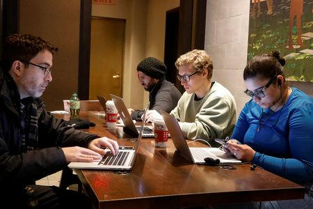 Customers use the internet at a Starbucks in the financial district in New York