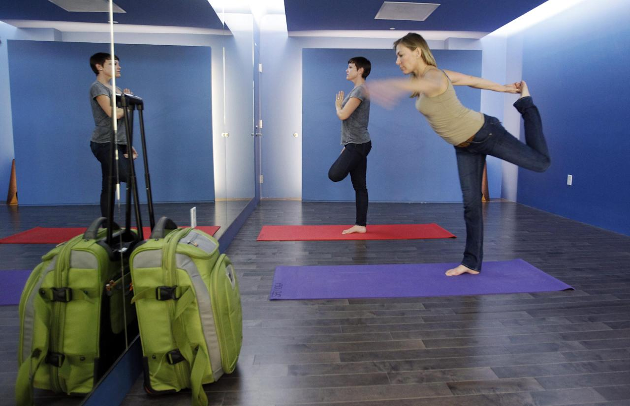 In this Friday, Jan. 27, 2012 photo, travelers Maria Poole, right, and Lindsey Shepard, practice yoga at San Francisco International Airport's new Yoga Room, in San Francisco. The quiet, dimly lit studio officially opened last week in a former storage room just past the security checkpoint at SFO's Terminal 2. Airport officials believe the 150-square-foot room with mirrored walls is the world's first airport yoga studio, said spokesman Mike McCarron. (AP Photo/Paul Sakuma)