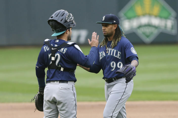 Seattle Mariners relief pitcher Keynan Middleton (99) high-fives catcher Luis Torrens (22) after their 4-3 win in the 10th inning of a baseball game against the Minnesota Twins, Saturday, April 10, 2021, in Minneapolis. (AP Photo/Stacy Bengs)