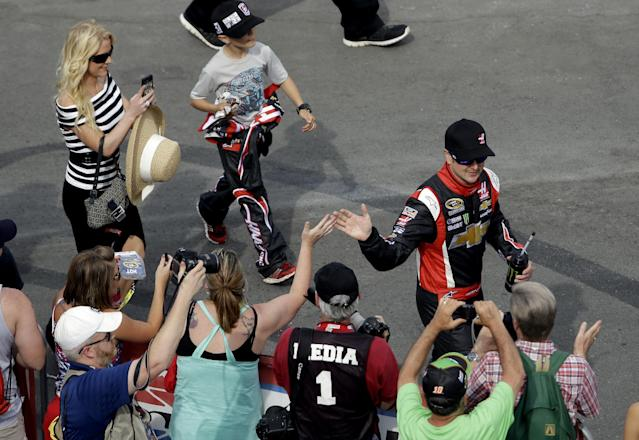 Driver Kurt Busch greets fans as he arrives for the NASCAR Sprint Cup series Coca-Cola 600 auto race at the Charlotte Motor Speedway in Concord, N.C., Sunday, May 25, 2014. Busch raced in the Indianapolis 500 earlier Sunday. (AP Photo/Gerry Broome)