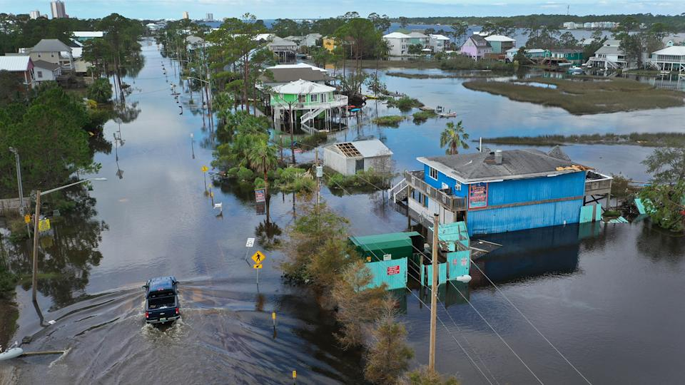 A vehicle passes through a flooded street after Hurricane Sally