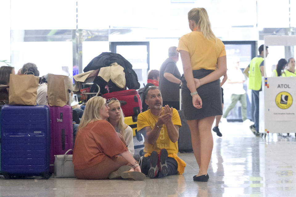 British passengers speak with Thomas Cook staff at Palma de Mallorca airport on Monday Sept. 23, 2019. Spain's airport operator AENA says that 46 flights have been affected by the collapse of the British tour company Thomas Cook, mostly in the Spanish Balearic and Canary archipelagos. (AP Photo/Francisco Ubilla)