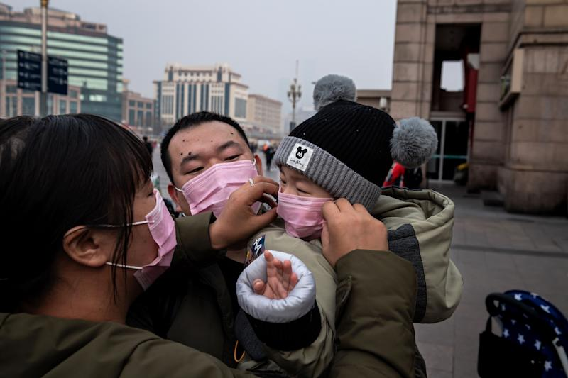 A mother (L) of a child (R) held by his father (C) adjust his protective mask to help stop the spread of a deadly virus which began in Wuhan peaks through a plastic curtain at the Beijing railway station in Beijing on January 27, 2020. - China on January 27 extended its biggest national holiday to buy time in the fight against a viral epidemic and neighbouring Mongolia closed its border, after the death toll spiked to 81 despite unprecedented quarantine measures. (Photo by NICOLAS ASFOURI / AFP) (Photo by NICOLAS ASFOURI/AFP via Getty Images)