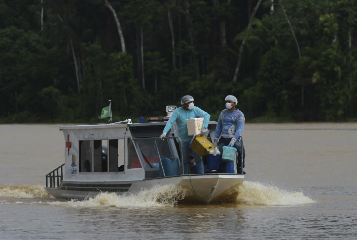 Healthcare workers Diego Feitosa Ferreira, 28, right, and Clemilton Lopes de Oliveira, 41, travel on a boat to the Santa Rosa community, Amazonas state, Brazil, Friday, Feb. 12, 2021, to vaccinate residents with the AstraZeneca COVID-19 vaccine. Getting the vaccine to the villages was important since most jungle communities have only basic medical facilities that aren't equipped to treat severe COVID-19 cases. (AP Photo/Edmar Barros)