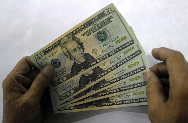 Employee shows dollar notes at foreign exchange unit at post office in Hyderabad