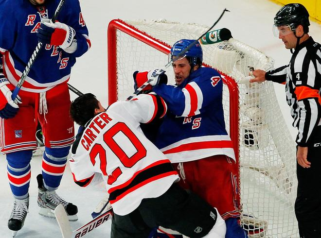 NEW YORK, NY - MAY 23:  Ryan Carter #20 of the New Jersey Devils exchanges blows with Michael Del Zotto #4 of the New York Rangers in Game Five of the Eastern Conference Final during the 2012 NHL Stanley Cup Playoffs at Madison Square Garden on May 23, 2012 in New York City.  (Photo by Paul Bereswill/Getty Images)