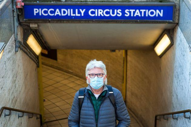 Close up color image depicting a senior caucasian male in his 60s wearing a protective face mask in the city during the coronavirus pandemic. The man is standing in the street outside Piccadilly Circus London underground station, and the architecture and lights of the city of London are defocused beyond. Room for copy space. (Photo: coldsnowstorm via Getty Images)