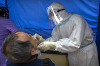 A worker wearing a protective suit swabs a man's throat for a coronavirus test at a community health clinic in Beijing, Sunday, June 28, 2020. China reported more than a dozen of new confirmed cases of COVID-19 on Sunday, all but a few of them from domestic transmission in Beijing, which has seen a recent spike in coronavirus infections. But authorities in the Chinese capital say a campaign to conduct tests on employees at hair and beauty salons across the city has found no positive cases so far, in a further sign that the recent outbreak has been largely brought under control. (AP Photo/Mark Schiefelbein)