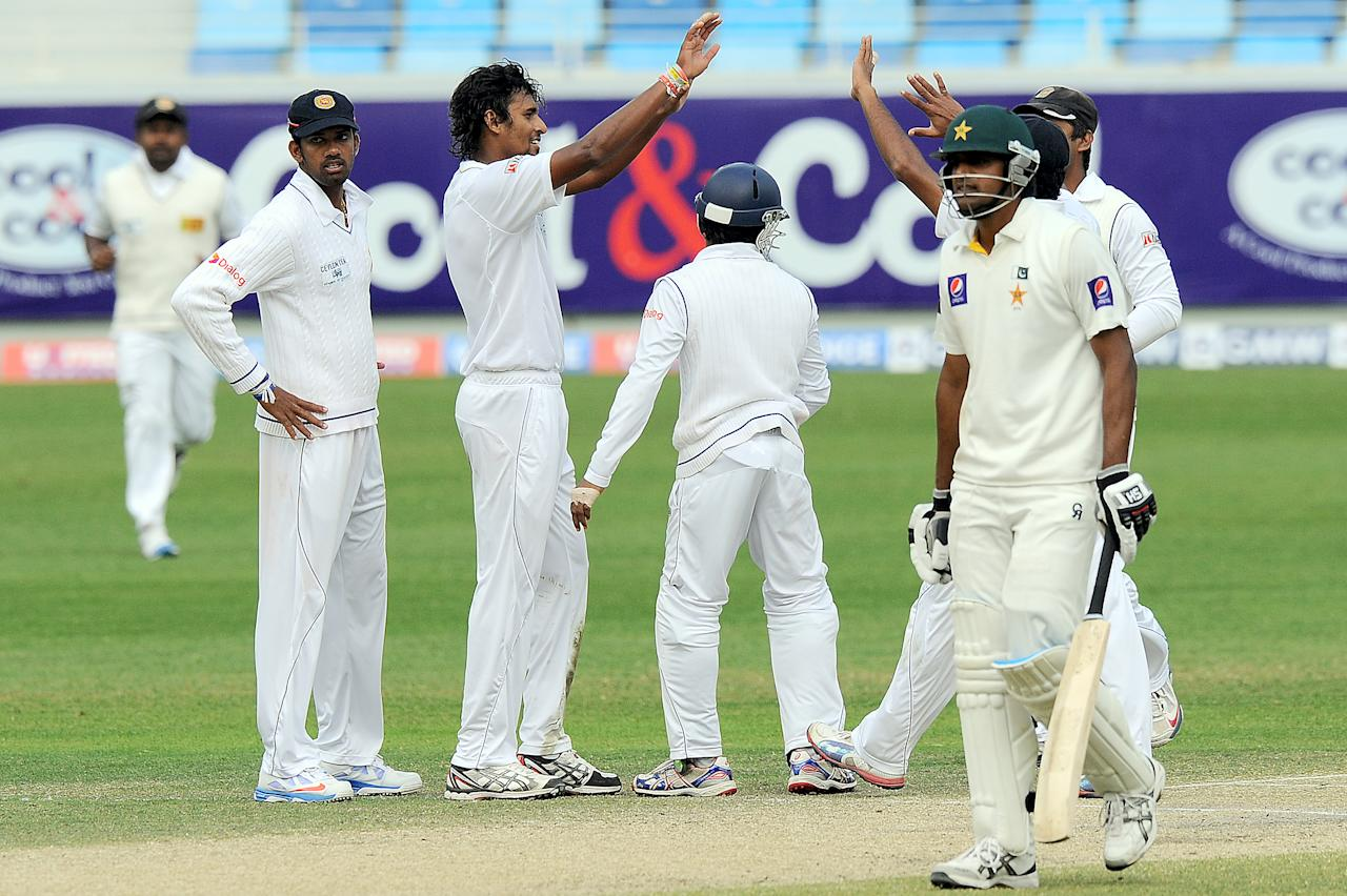 Sri Lankan bowler Suranga Lakmal  (C) celebrates with teammates after dismissing of Pakistan batsman Rahat Ali (R) during the final day of the second cricket Test match between Pakistan and Sri Lanka at the Dubai International Cricket Stadium in Dubai on January 12, 2014. AFP PHOTO/Ishara S. KODIKARA