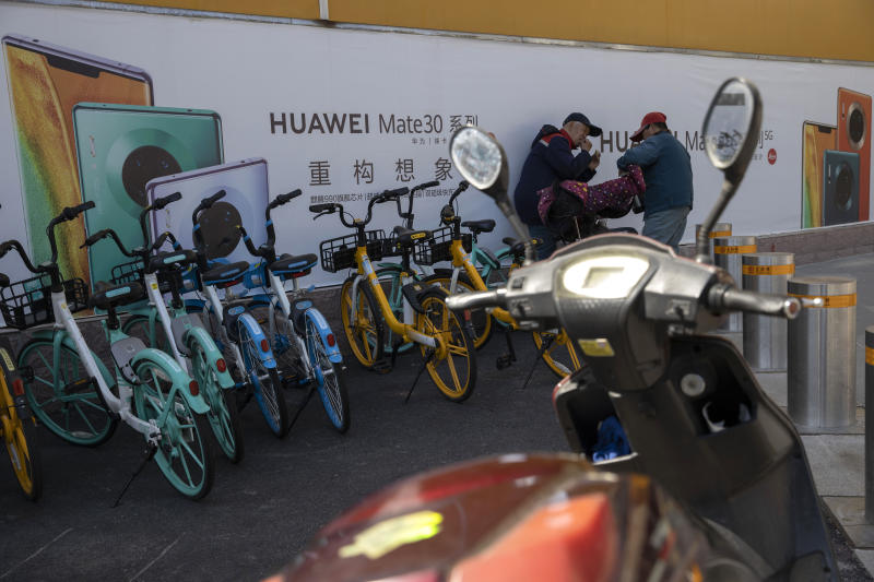 In this photo taken Sunday, March 22, 2020, men chat near advertisements for Huawei mobile phones in Beijing. Chinese tech giant Huawei says Tuesday, March 31, 2020, its 2019 sales rose 19.1% over a year earlier despite U.S. sanctions that hampered its smartphone and network equipment businesses. The company is embroiled in a series of disputes with Washington, which says Huawei is a security risk, an accusation it denies. (AP Photo/Ng Han Guan)