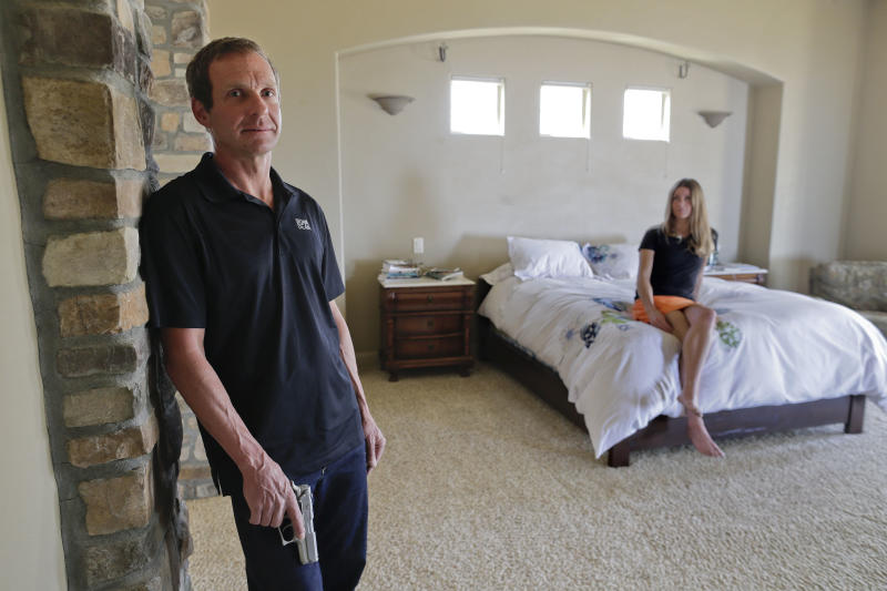 In this Saturday, April 6, 2013 photo, Eric Martin poses for a photo with his fiancee, Rachel Cieslewicz, at their home in St. George, Utah. In late March 2013, Martin chased down an intruder to their home and held him at gunpoint with the 9-mm Smith & Wesson handgun that he keeps in his bedside night stand, until the police arrived. In two decades of debate over guns in the U.S., intense disagreement has long clouded seemingly straight-forward questions of how, exactly, Americans use firearms to defend themselves and how often. But listening to Martin's account of the incident shows how the uncertainty of the abstract plays out with very real consequences. (AP Photo/Julie Jacobson)