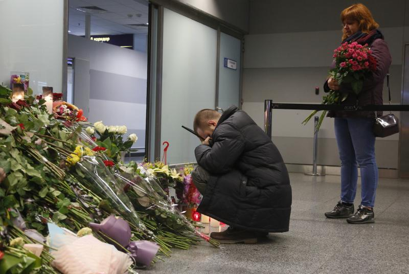 The partner of Julia Sologub, a member of the flight crew of the Ukrainian 737-800 plane that crashed on the outskirts of Tehran, reacts as he holds a portrait of her at a memorial inside Borispil international airport outside in Kyiv, Ukraine, Friday, Jan. 10, 2020. Iran on Friday denied Western allegations that one of its own missiles downed a Ukrainian jetliner that crashed outside Tehran, and called on the U.S. and Canada to share any information they have on the crash, which killed all 176 people on board. (AP Photo/Efrem Lukatsky)