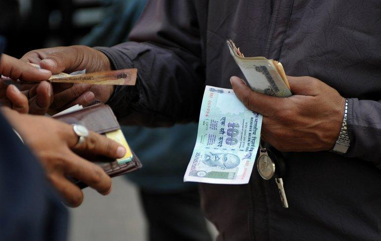 A parking lot employee receives payment from a customer in New Delhi on December 15, 2011. India's currency's woes all add up to bad news for the left-leaning Congress government led by Premier Manmohan Singh, which is struggling to rein in subsidies and overspending under pressure from international ratings agencies