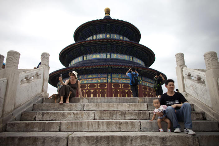 In this Aug. 7, 2013 photo, a foreign tourist, left, takes photos of herself as she tours the Temple of Heaven in Beijing. China, one of the most visited countries in the world, has seen sharply fewer tourists this year, with worsening air pollution partly to blame. (AP Photo/Alexander F. Yuan)