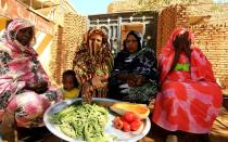 FILE PHOTO: Women sit together as they prepare food for their families in Khartoum north