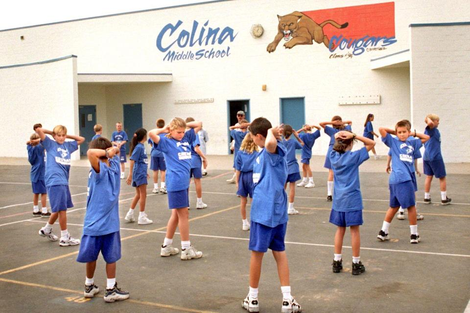 <p>Middle school kids wear gym uniforms while stretching during P.E. class.</p>