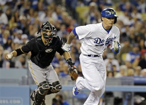 Los Angeles Dodgers' Justin Sellers, right, heads for first after striking out swinging as Pittsburgh Pirates catcher Russell Martin throws to first in the fifth inning of a baseball game in Los Angeles, Saturday, April 6, 2013. (AP Photo/Reed Saxon)