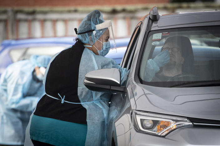 A driver has a COVID-19 test at a driver through clinic in Auckland, New Zealand, Thursday, Aug. 19, 2021. Japan, Australia and New Zealand all got through the first year of the coronavirus pandemic in relatively good shape, but now are taking diverging paths in dealing with new outbreaks of the fast-spreading delta variant. (Jason Oxenham/New Zealand Herald via AP)