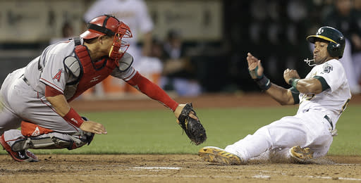Oakland Athletics' Chris Young, right, slides beneath the tag of Los Angeles Angels catcher Hank Conger to score in the fourth inning of a baseball game Thursday, July 25, 2013, in Oakland, Calif. Young scored on a hit by Derek Norris. (AP Photo/Ben Margot)