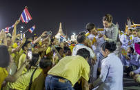 King Maha Vajiralongkorn, center left listens to a supporter as Queen Suthida, in kings right watches in Bangkok, Thailand, Sunday, Nov. 1, 2020. Under increasing pressure from protesters demanding reforms to the monarchy, Thailand's king and queen met Sunday with thousands of adoring supporters in Bangkok, mixing with citizens in the street after attending a religious ceremony inside the Grand Palace. (AP Photo/Wason Wanichakorn)
