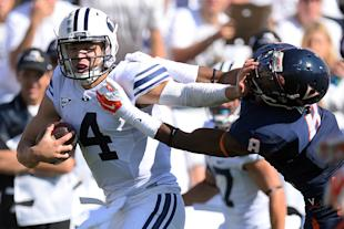BYU QB Taysom Hill (L) stiff-arms a Virginia defender during his team's win on Saturday. (Photo: USAT)