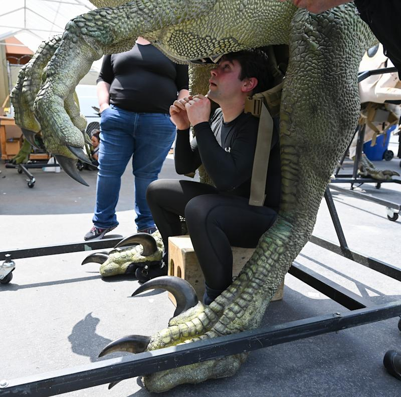 Robert Gardner bears the weight of a velociraptor in an attached backpack while operating the dinosaur in the