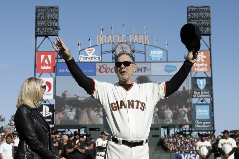 San Francisco Giants manager Bruce Bochy, center, gestures toward fans next to his wife Kim during a ceremony honoring Bochy after a baseball game between the Giants and the Los Angeles Dodgers in San Francisco, Sunday, Sept. 29, 2019. (AP Photo/Jeff Chiu, Pool)