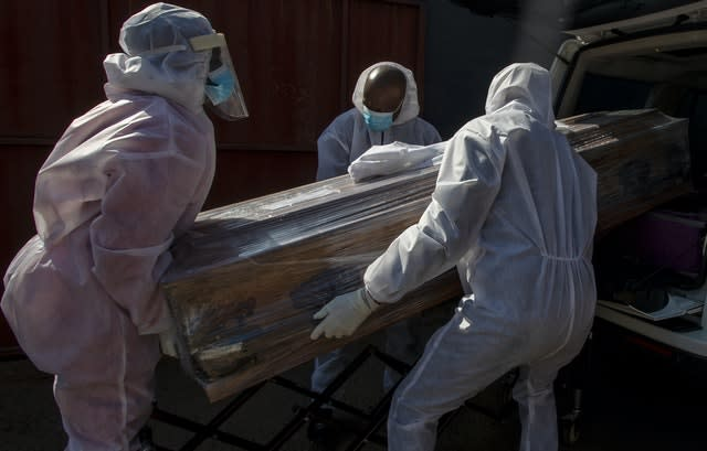 Funeral home workers in protective suits carry the coffin of a woman who died from Covid-19 into a hearse in Katlehong, near Johannesburg, South Africa (Themba Hadebe/AP)