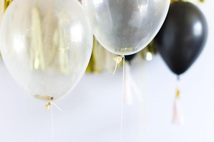 """<p>Here's a fun way to incorporate your gifts into your decorations! Fill a clear balloon with a handful of confetti and no more than five rolled-up bills, then have the balloons inflated at a party supply store. This gift-wrapping idea doesn't just look pretty, it helps create a fun, festive atmosphere every time someone """"opens"""" their gift. <i>(Photo: <a href=""""http://www.balloontime.com/party-ideas/occasions/graduation-money-balloons/"""" rel=""""nofollow noopener"""" target=""""_blank"""" data-ylk=""""slk:Balloon Time"""" class=""""link rapid-noclick-resp"""">Balloon Time</a>)</i><br></p>"""
