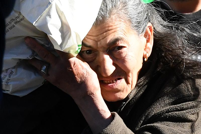 Mother of the Bondi Hoarders, Mary Bobolas, tried to hide from cameras as she leaves the Downing Centre Local Court. Source: AAP Image.