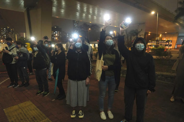 Supporters hold flash lights after activists charged with conspiracy were released on bail at a court in Hong Kong, Friday, March 5, 2021. Four of the 47 pro-democracy activists charged with conspiracy to commit subversion were released on bail Friday, after prosecutors dropped an appeal against the court's decision to grant them bail. (AP Photo/Kin Cheung)
