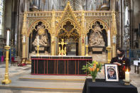 A photograph of Britain's Prince Philip, the Duke of Edinburgh, is displayed alongside the nave at Westminster Abbey, London, Saturday April 10, 2021, which has been dressed in black to mark his death. (Dominic Lipinski/PA via AP)