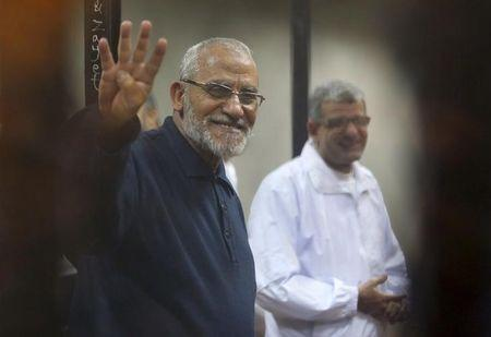 Muslim Brotherhood's Supreme Guide Mohamed Badie flashes the Rabaa sign as he stands behind bars during his trial with ousted Egyptian President Mohamed Mursi and other leaders of the brotherhood at a court on the outskirts of Cairo