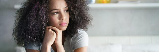 Lonely young woman sitting on bed. Depressed girl at home, looking away with sad expression.