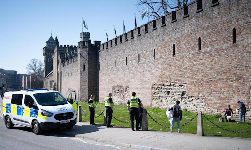 Police move on a group of three people from Cardiff castle on 26 March.