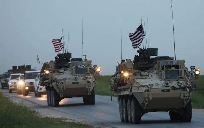 US military vehicles and Kurdish fighters from the People's Protection Units (YPG) drive in the town of Darbasiya next to the Turkish border, Syria. - Reuters