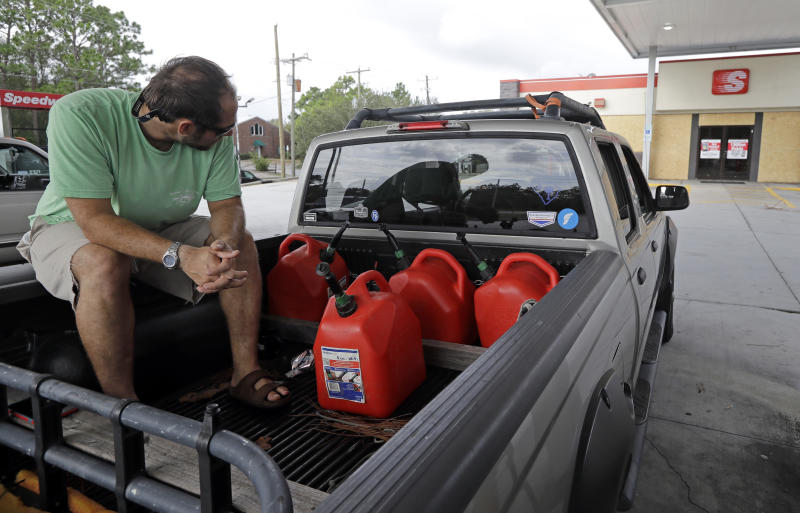 FILE - In this Sept. 17, 2018, file photo Nick Monroe waits at a gas station in hopes a truck will bring fuel for his vehicles and generator near Wilmington, N.C., in preparation for Hurricane Florence. Backup power options range from gasoline-powered portable generators, which can cost $1,000 or more, to solar panels plus batteries, which cost tens of thousands of dollars to purchase and install. (AP Photo/Chuck Burton, File)