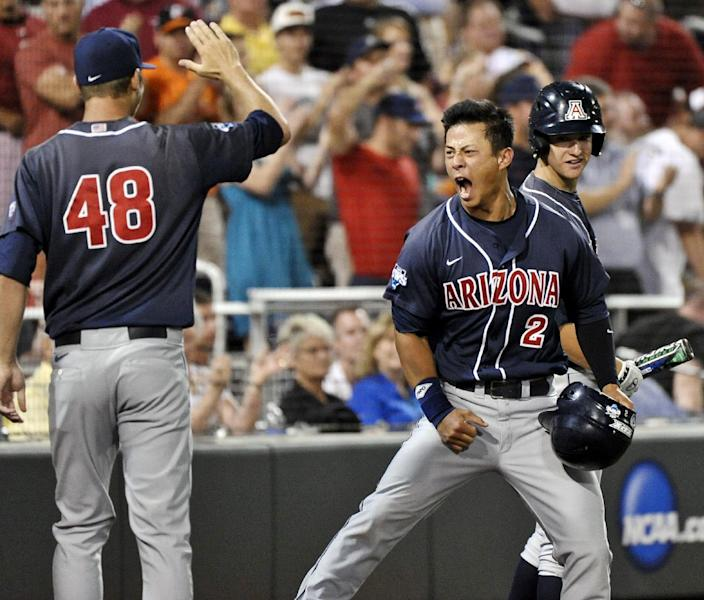 Arizona's Robert Refsnyder (2) celebrates with Konner Wade (48) after scoring the go-ahead run against South Carolina on a double by Brandon Dixon in the ninth inning of Game 2 of the NCAA College World Series baseball finals in Omaha, Neb., Monday, June 25, 2012. (AP Photo/Ted Kirk)
