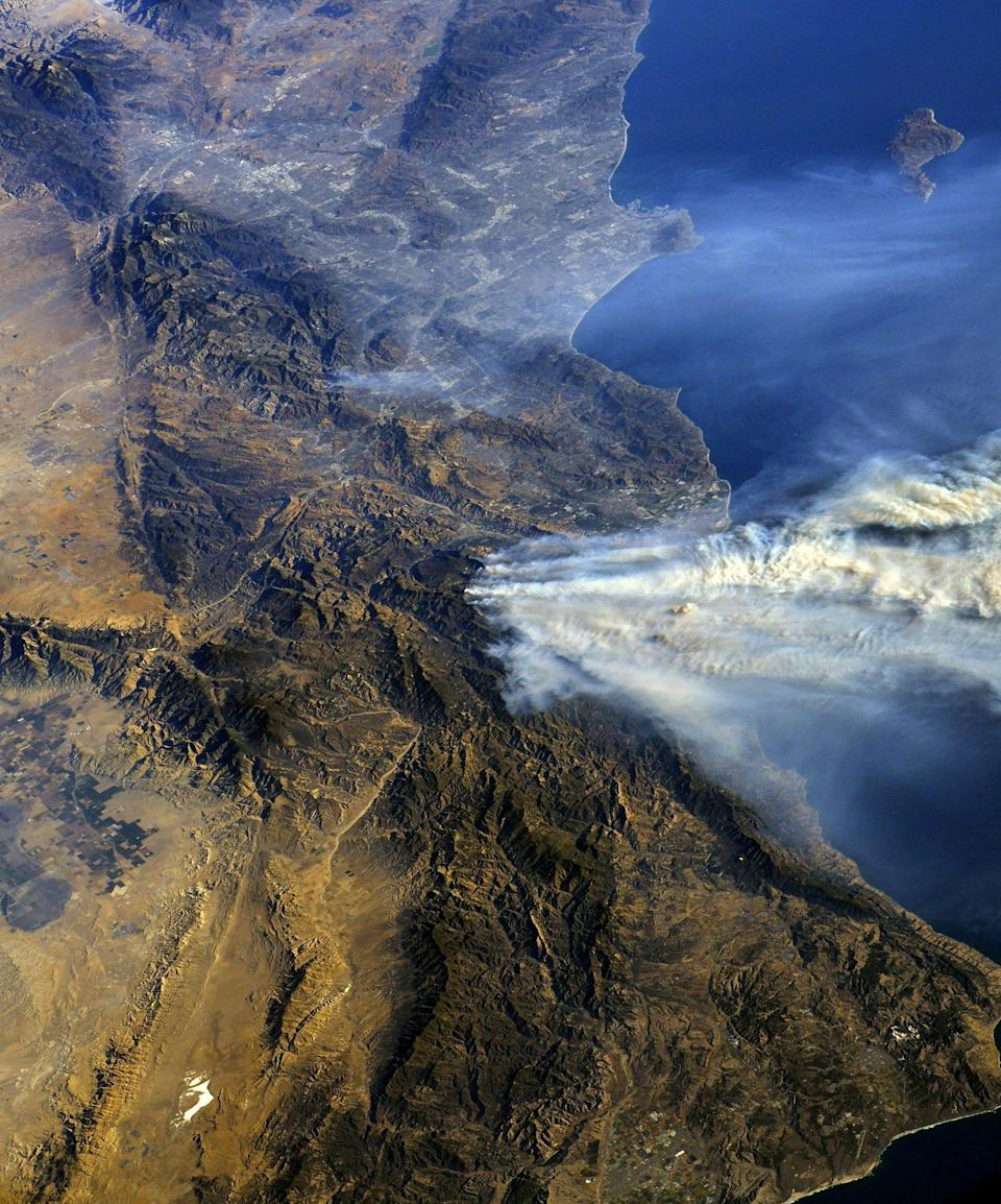 <p>Taken from the ISS, this photo shows the wildfire spreading across California's hills (Picture: Reuters) </p>