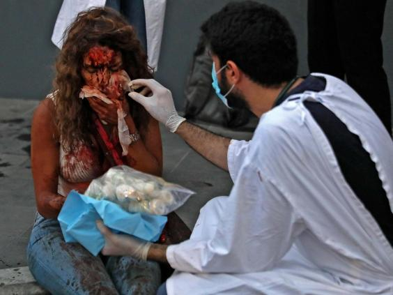 A wounded woman receives help outside a hospital following an explosion in the Lebanese capital Beirut (AFP via Getty Images)