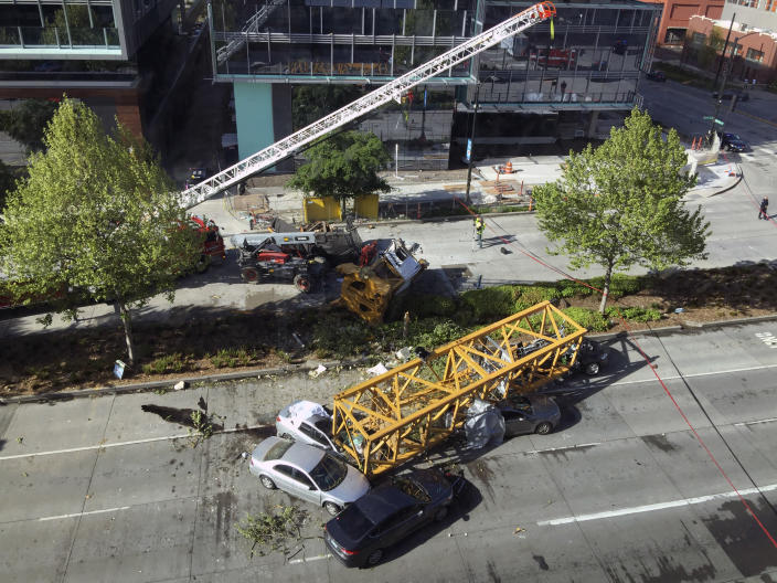 Fire and police crew members work to clear the scene where a construction crane fell from a building on Google's new Seattle campus crashing down onto one of the city's busiest streets and killing multiple people on Saturday, April 27, 2019. (AP Photo/Frank Kuin)