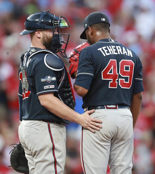 Atlanta Braves catcher Brian McCann, left, confers with pitcher Julio Teheran just before Teheran gave up a winning sacrifice fly to St. Louis Cardinals catcher Yadier Molina to score Kolten Wong during the 10th inning of Game 4 of a baseball National League Division Series, Monday, Oct. 7, 2019, in St. Louis. (Curtis Compton/Atlanta Journal-Constitution via AP)