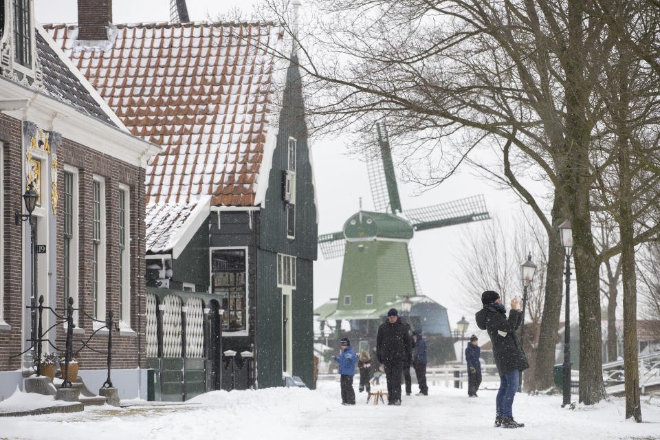 People take a stroll at the Zaans Museum in Zaandam, Netherlands, Sunday, Feb. 7, 2021. Snow and strong winds pounded The Netherlands, with more snow and cold temperatures expected in the days ahead. (AP Photo/Peter Dejong)