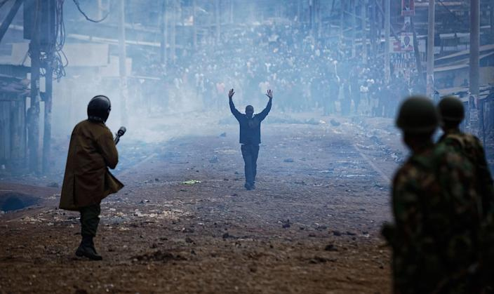 <p>AUG. 10, 2017 – A man seeking safety walks with his hands in the air through a thick cloud of tear gas towards riot police, as they clash with protesters throwing rocks in the Kawangware slum of Nairobi, Kenya. International observers on urged Kenyans to be patient as they awaited final election results following opposition allegations of vote-rigging, but clashes between police and protesters again erupted in Nairobi. (Photo: Ben Curtis/AP) </p>
