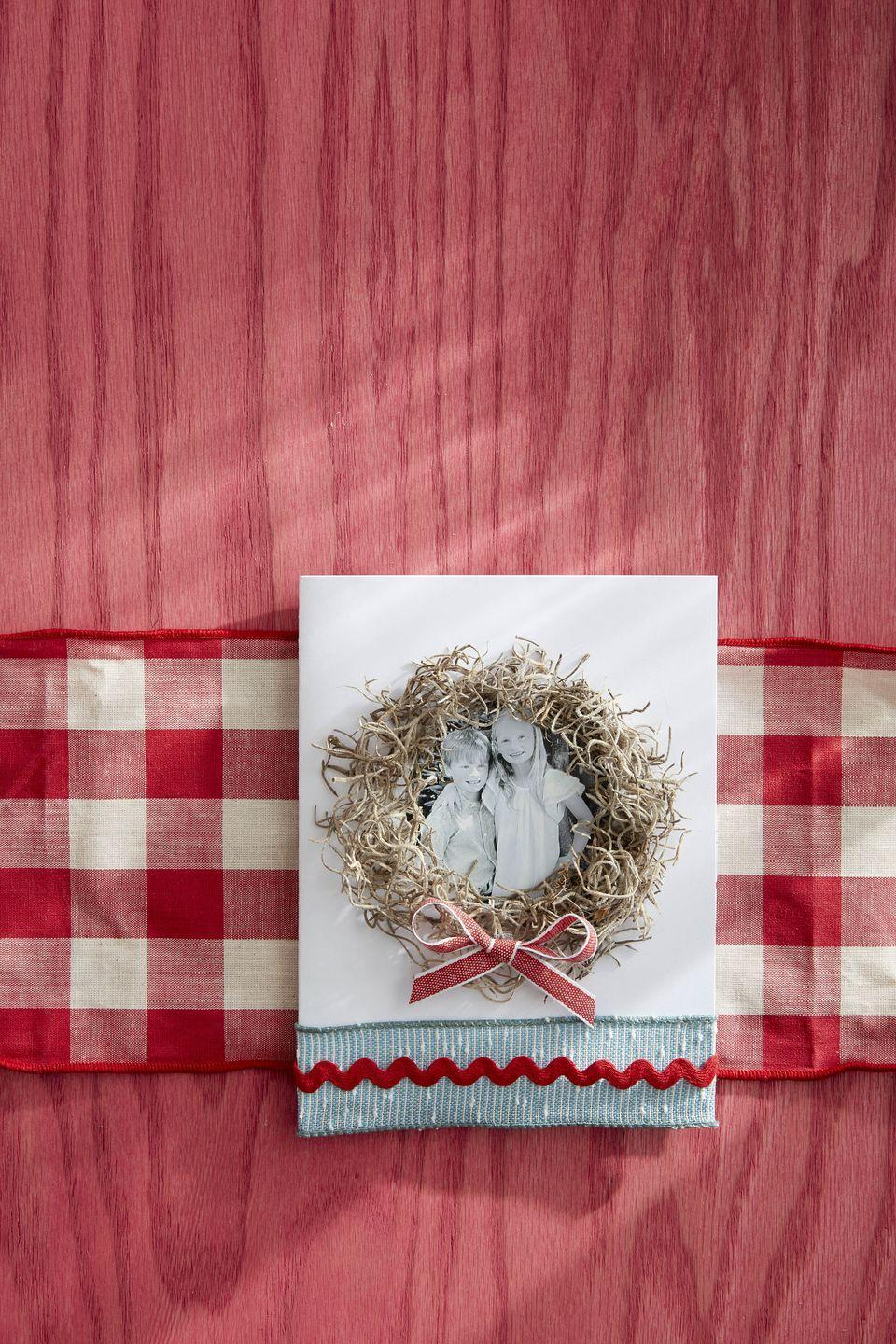 """<p>Send greetings from the kids or the whole family by making this photo card with it's natural Spanish moss wreath accent.</p><p><strong>To make:</strong> Cut a black-and-white photograph of the kids, pets, or the entire family in a circle; glue to the front of a plain card. Attach lengths of Spanish moss around the picture with hot glue to create a wreath. Attach a mini bow to the bottom of the wreath with hot glue. Add a ribbon and rick rack flair to the bottom of the card.</p><p><a class=""""link rapid-noclick-resp"""" href=""""https://www.amazon.com/SuperMoss-26911-Spanish-Moss-Natural/dp/B00I6AJ57A/ref=sr_1_1_sspa?tag=syn-yahoo-20&ascsubtag=%5Bartid%7C10050.g.3872%5Bsrc%7Cyahoo-us"""" rel=""""nofollow noopener"""" target=""""_blank"""" data-ylk=""""slk:SHOP SPANISH MOSS"""">SHOP SPANISH MOSS</a></p>"""
