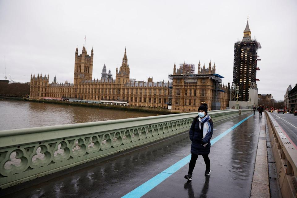 A woman walks a nearly deserted London street as a particularly virulent strain of the coronavirus swept parts of Britain in December. Photo: Reuters