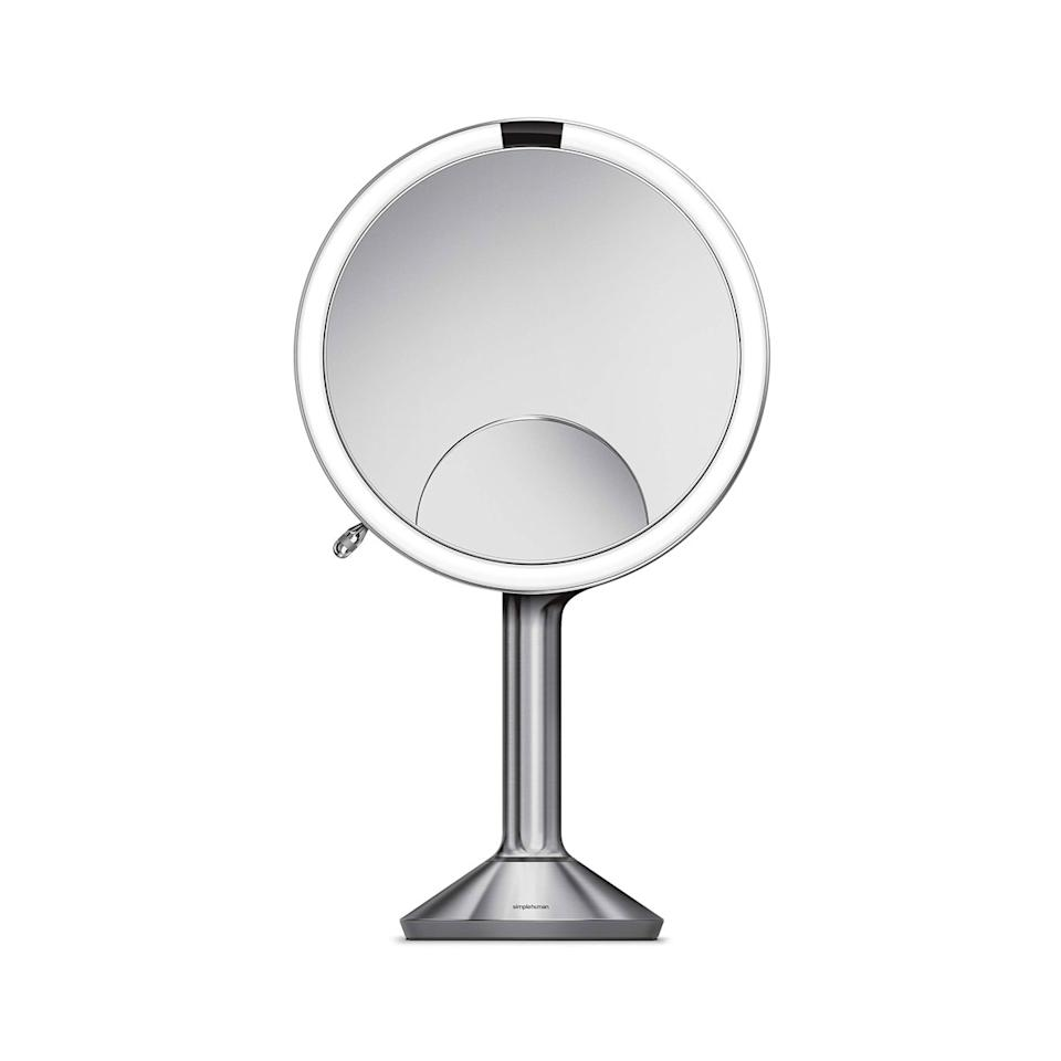 """This beauty is basically the Cadillac of lighted makeup mirrors—and it comes with the price tag to confirm it. But what it sets you back financially, it more than makes up for with its high-tech capabilities and five-year warranty. First, let's talk about its magnification. It comes with three different views: 1x, 5x, and a mini 10x half-moon that's particularly great for seeing every single lash as you put on mascara. Its lighting capabilities are also unreal. You can run your finger along the rim of the mirror to make the lighting dimmer or brighter. And it automatically lights up whenever you look into it. My favorite part, though, is that it's cordless. You charge it with a regular USB plug, and it holds its juice for up to five weeks. My colleagues can confirm I use it an obscene amount at my desk. I don't know what I'd do without it. <em>—Lindsay Schallon, senior beauty editor</em> $301, Bed Bath & Beyond. <a href=""""https://www.bedbathandbeyond.com/store/product/simplehuman-reg-sensor-8-inch-sensor-mirror-trio/5159459?"""">Get it now!</a>"""