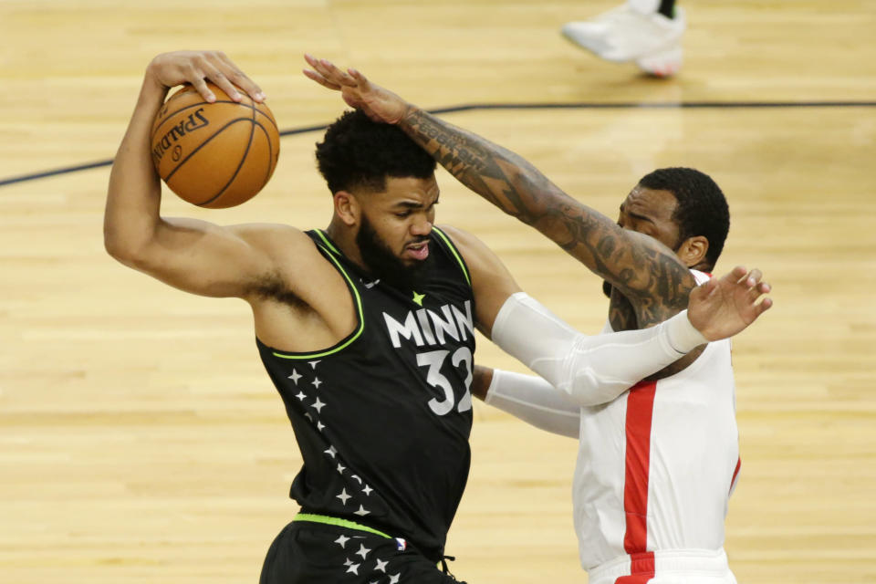 Minnesota Timberwolves center Karl-Anthony Towns (32) protects the ball from Houston Rockets guard John Wall (1) in the first quarter during an NBA basketball game, Friday, March 26, 2021, in Minneapolis. (AP Photo/Andy Clayton-King)