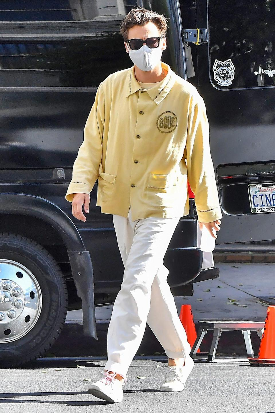 <p>Harry Styles steps out in a yellow shirt as he strolls to the set of <i>Don't Worry Darling</i> in L.A. on Wednesday. </p>